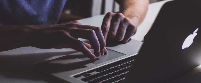Ein Mann tippt mit seinen Händen auf einer Laptop-Tastatur