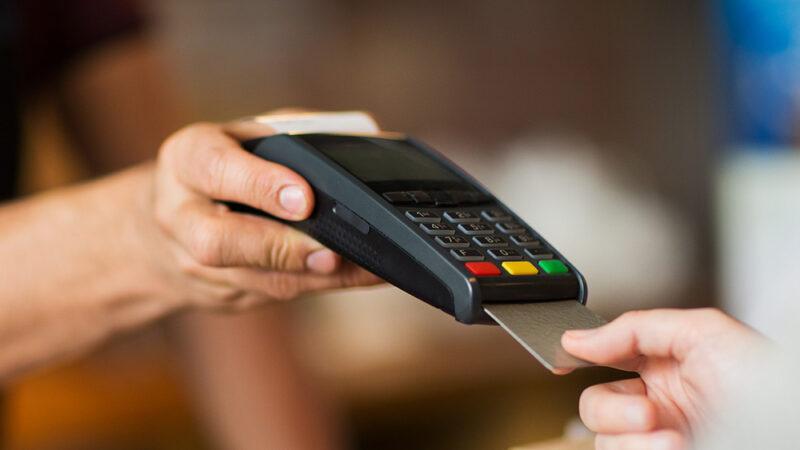 Ein Mann steckt seine EC-Karte im Geschäft in ein Kartenlesegerät